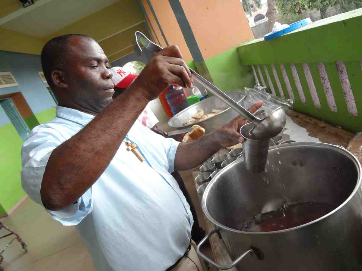 Catholic Missionary serving soup in Haiti