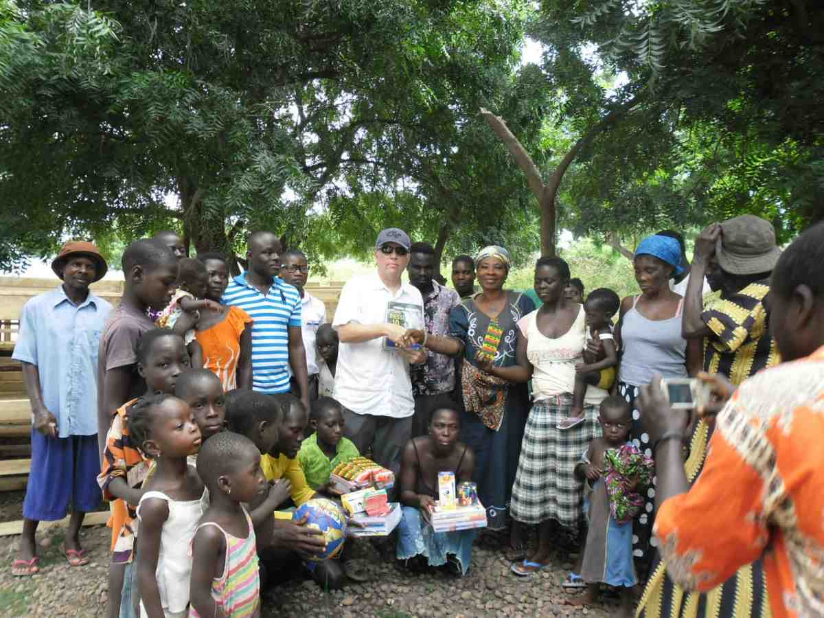 Mike Barry seen center giving school supplies to GIS - Ghana