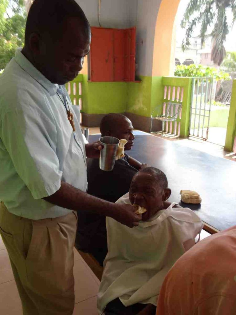 Catholic Missionary feeding elderly man