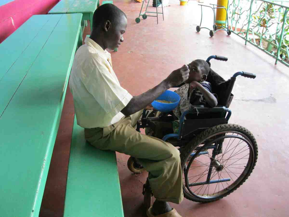 Catholic Missionary feeding a disabled child in Kenya
