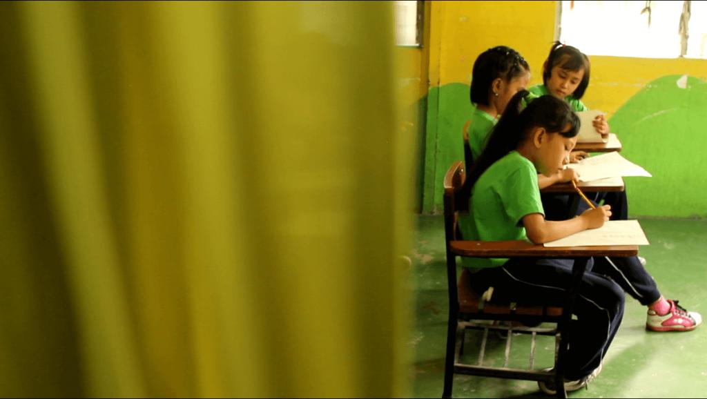 mano amiga philippines student working at desk