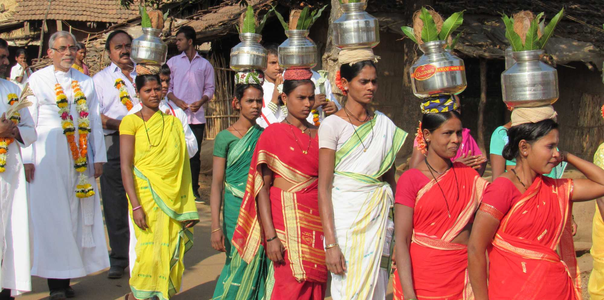 Women Carrying water jugs on their jead