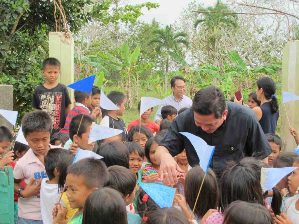 Deacon Rick passing out rosaries to children - Philippines