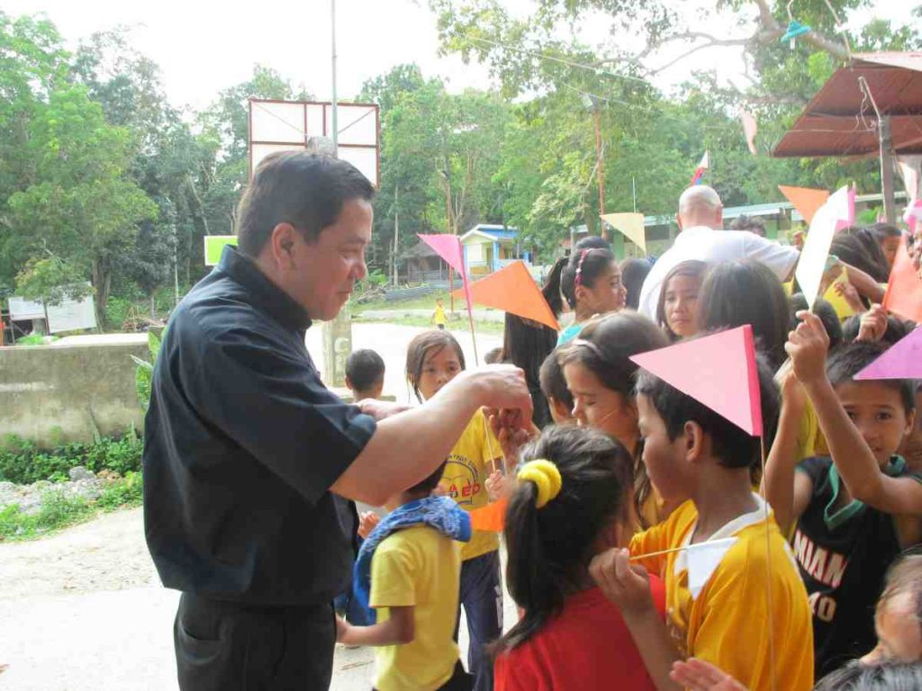Deacon Rick passing out rosaries to the school children - Philippines
