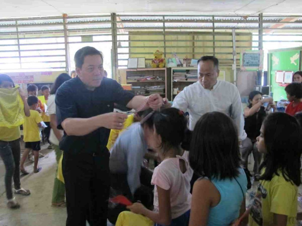 Deacon Rick placing rosary over child - Philippines