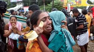 Indian woman crying with child over flooding in Kerala, India