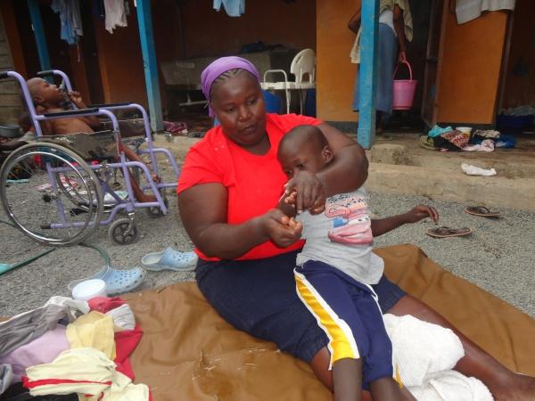 Volunteer caring for disabled child - Kenya
