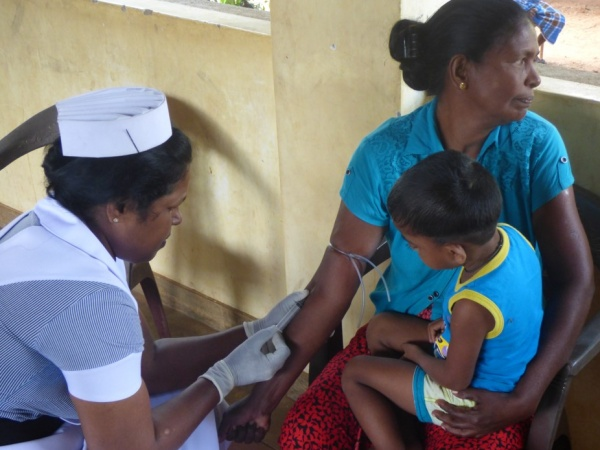 Sri Lanka Medical Mission - a patient undergoes a blood draw - Giribawa