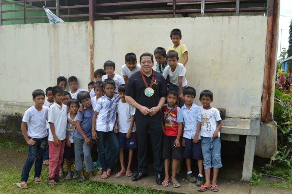 Executive Director Deacon Rick Medina stands with students from Lonoy Elementary - Philippines