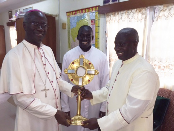 Bishop Kwofie (left) and Fr. Anthony Eshun (center) receive a monstrance from Msgr. Simon (right)