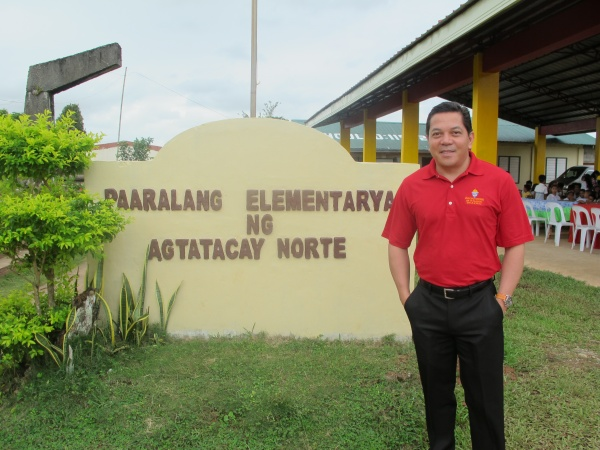 Executive Director Deacon Rick Medina stands outside Agtatacay Notre Elementary - Philippines
