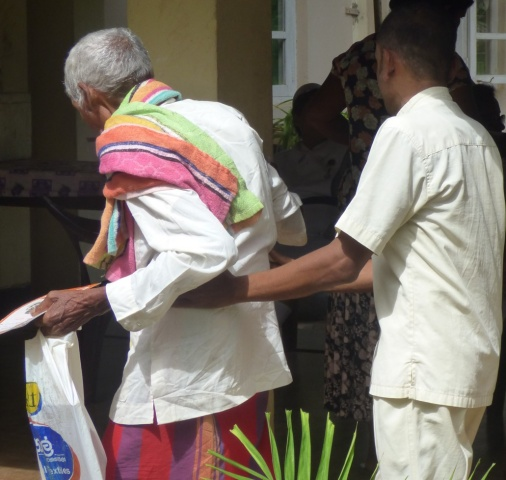 Sri Lanka Medical Mission - an elderly man is assisted into the clinic - Giribawa