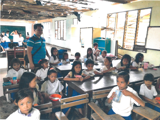 Children learn in debris of their classroom after Typhoon Haiyan - Philippines