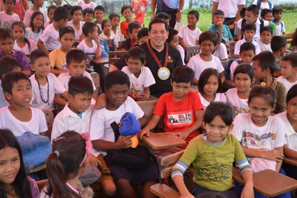 Executive Director Deacon Rick Medina sits with students from Lonoy Elementary - Philippines