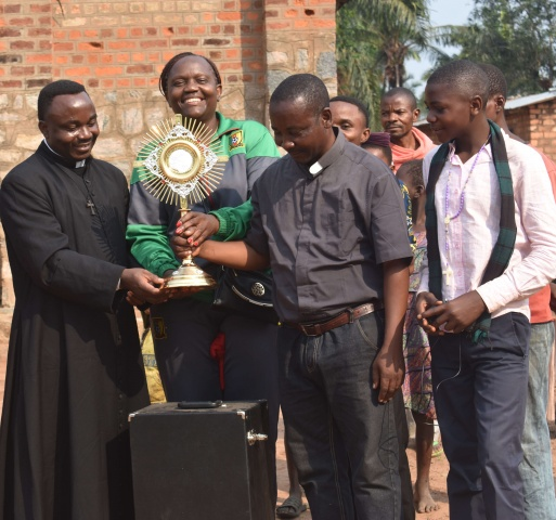 Fr. Donatien and Ide give the monstrance to Fr. Vincent