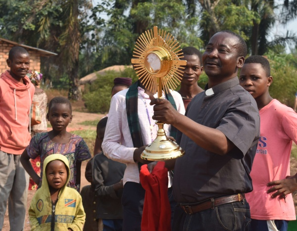 Fr. Vincent shows the monstrance to the villagers gathered around