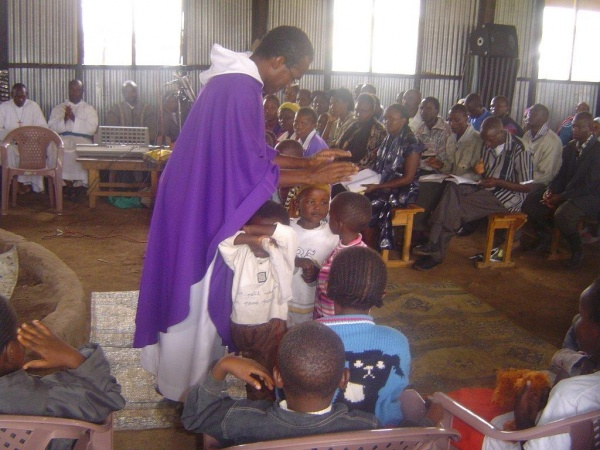 A Missionary of the Poor priest blessing the little children - Kenya