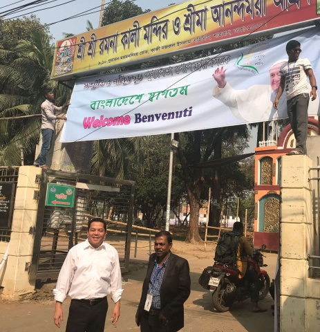 Bangladesh - Deacon Rick with his translator at the entrance to Suhrawardy Udyan Park, where Pope Francis ordained 16 new priests