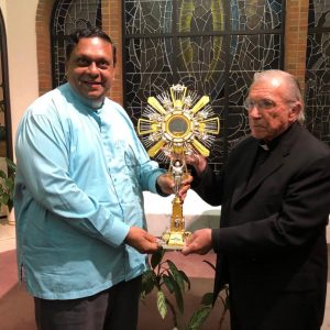 Close up of Fr. David Gomes receiving a new monstrance