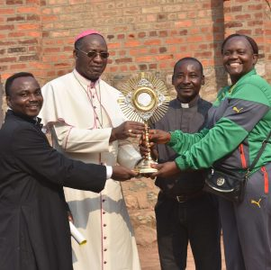 Bishop Celestin, CWM partner Ide Maka, and Fr. Donatien give Fr. Vincent a new monstrance for his parish, Our Lady of Seven Sorrows in Ndekesha Kazumba, DR Congo