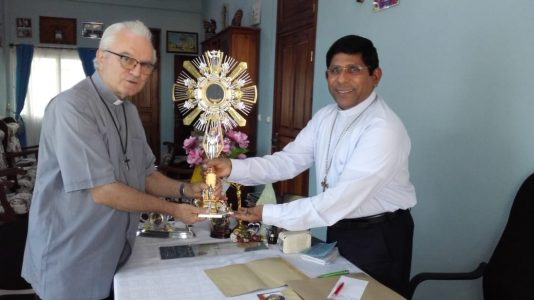 Bishop Varkey presents monstrance to a priest in Madagascar