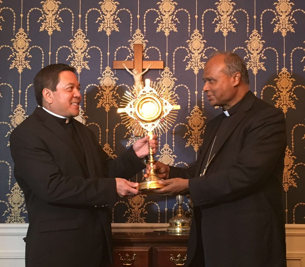 Deacon Rick Medina presents a new monstrance to Archbishop George Antonysamy