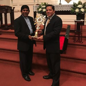 Deacon Rick Medina presents Bishop George Varkey of Madagascar with a new monstrance
