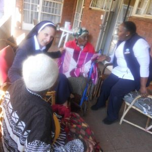 A Sister of Nazareth and staff member sit with hospice patients at Nazareth House Johannesburg
