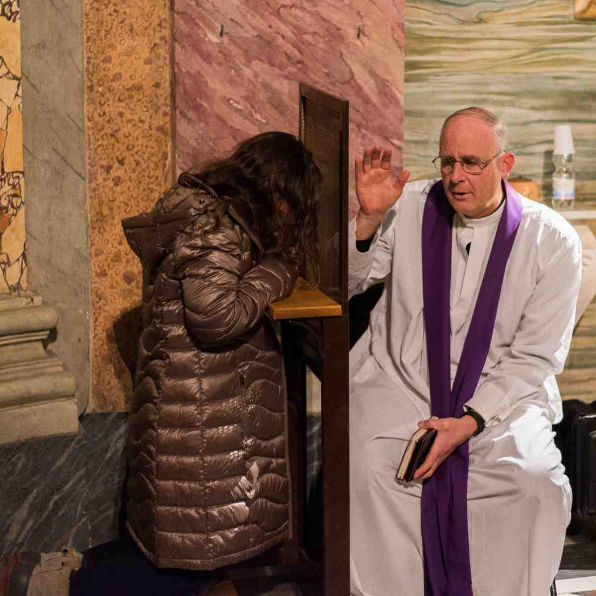 A priest hears a confession in Rome. The Catholic priest is the living example of God's love in our lives.