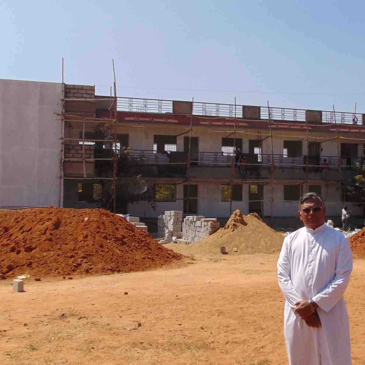 Fr. Selvaraj in front of the new postulant dorm you helped build!