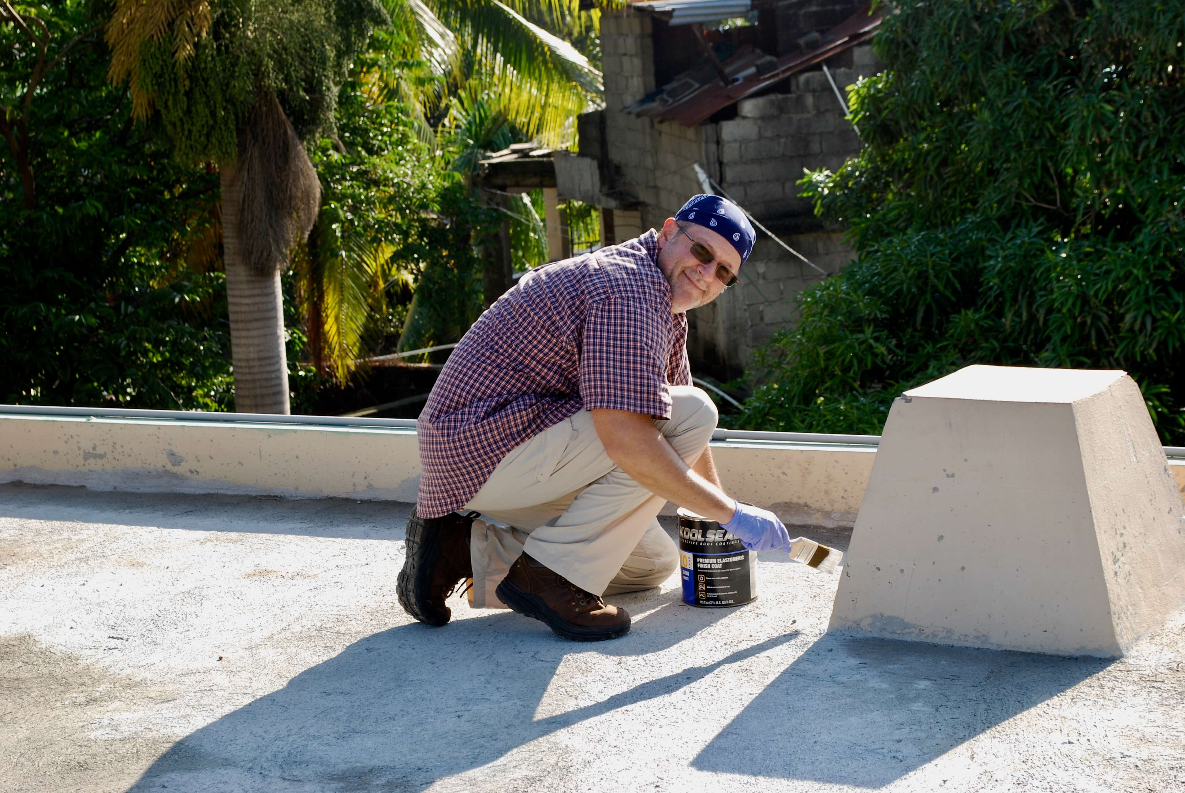 Board Member Nick Donnelly helps paint the roof at the Missionaries of the Poor compound in Haiti