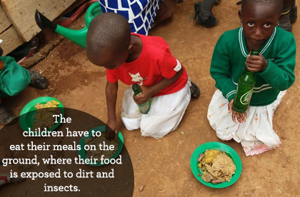 The children have to eat their meals on the ground, where their food is exposed to dirt and insects.
