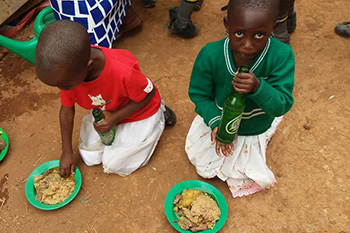 Uganda - Children eat on the ground without a dining hall to protect them from the elements at St. Philomena School