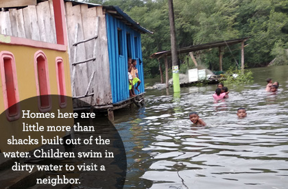 Homes here are little more than shacks built out of the water. Children swim in dirty water to visit a neighbor.