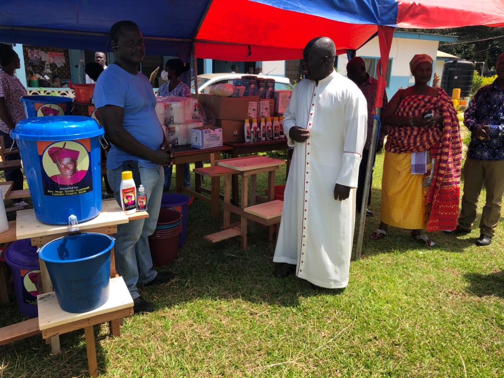 4. Msgr. Simon oversees the distribution of supplies. The blue bucket pictured here is a Victoria bucket, which are used throughout Ghana to provide hand-washing stations.