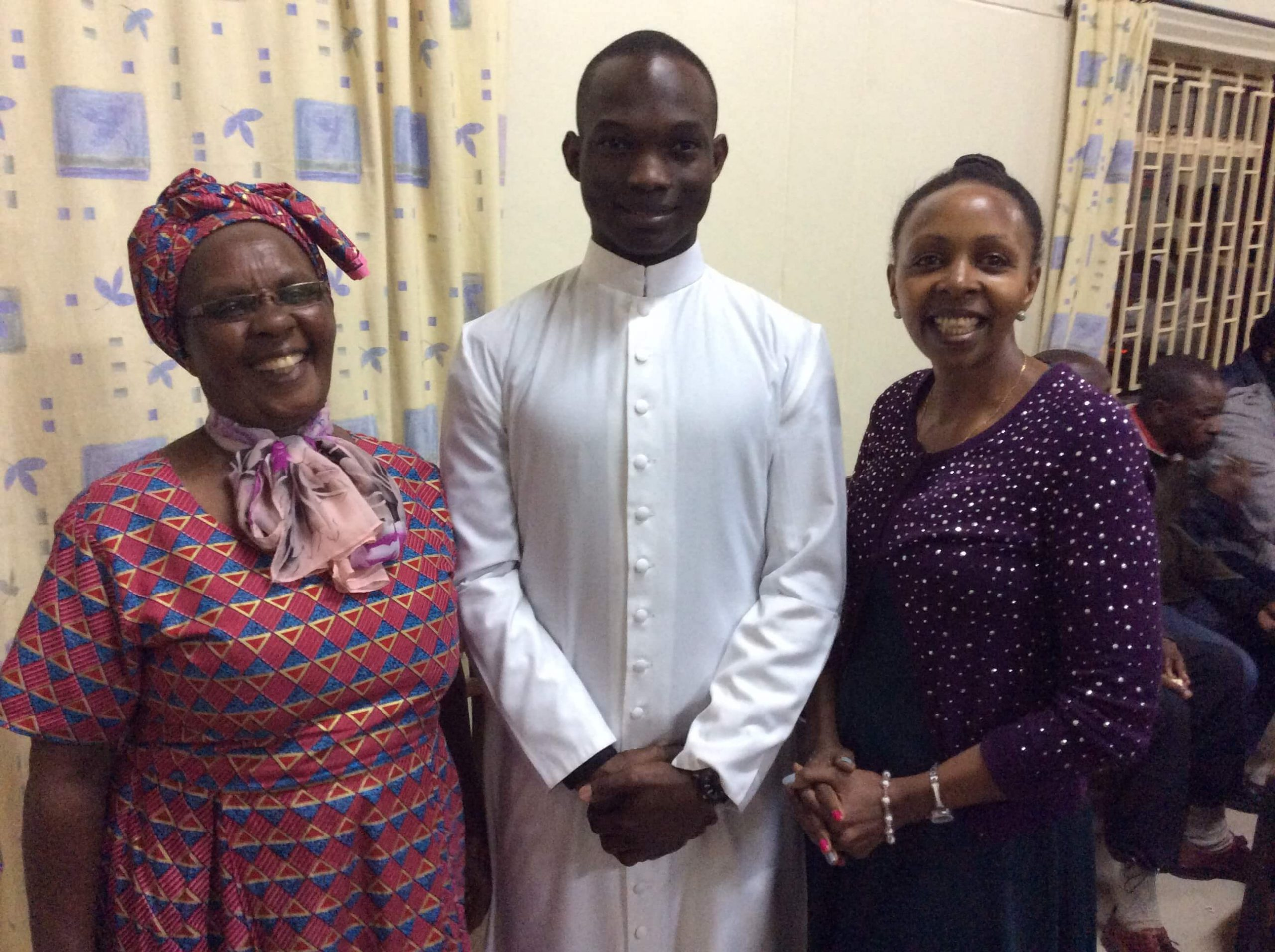 A young seminarian with his mom and sister