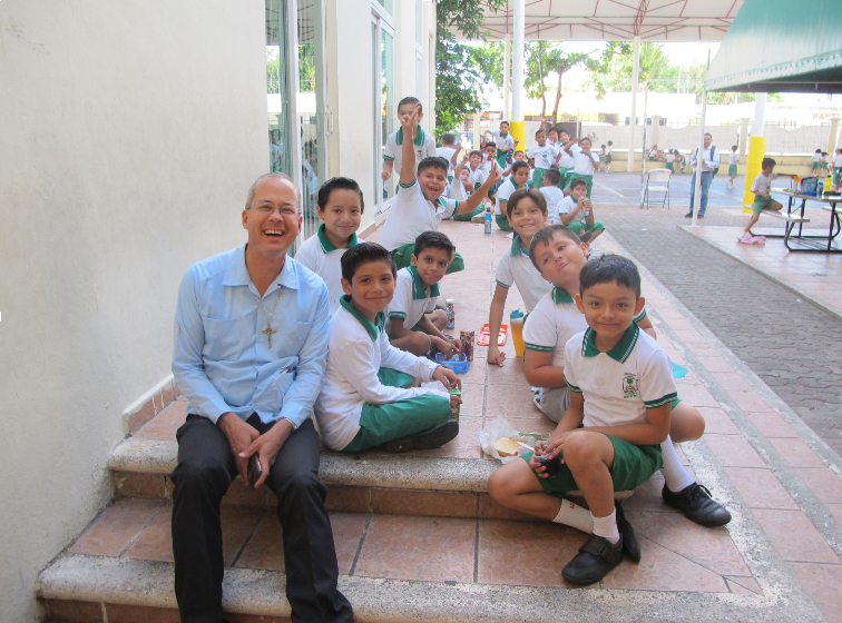 Father Patrick having lunch with children at Mano Amiga Mexico School