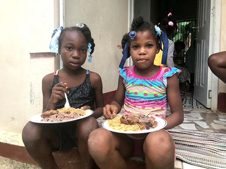 girls in Haiti eating a hot meal